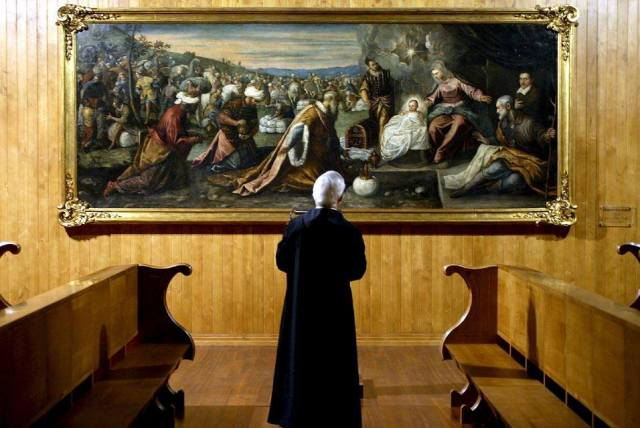 A priest watches the Tintoretto oil painting 'The Worship of the Magi' that was given to the Portuguese benedictine Singeverga Monastery by a citizen of Lisbon in 2003, in Santo Tirso, Portugal. EPA/ESTELA SILVA © 2007