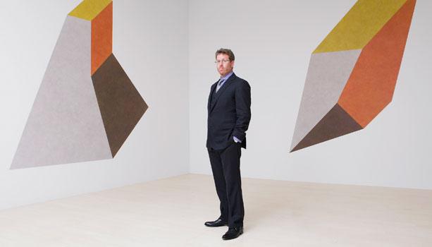 佩斯画廊主Marc Glimcher站在佩斯旗舰店:57街画廊中的两幅Sol LeWitt绘画之间