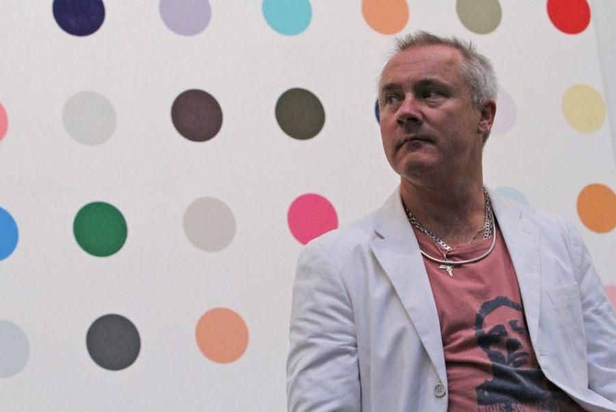 """2012年1月11日周三,高古轩-纽约切尔西,英国艺术家达明•赫斯特(Damien Hirst)在其个展""""达明•赫斯特:1986-2011圆点系列回顾展""""(Damien Hirst: The Complete Spot Paintings 1986 – 2011)新闻发布会上于参展作品《甲基胞嘧啶1号》(1-Methylcutosine)前留影。为了此次大规模联展,高古轩动用了其全球11家画廊同时展出赫斯特的圆点画。AP摄影/Mary Altaffer."""